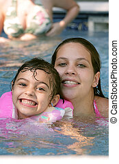 Mother child in pool - A young mother with her child in a...