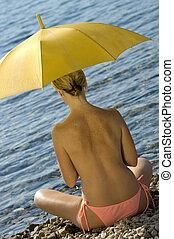 umbrella - A woman holding a yellow umbrella on a beach