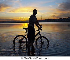 biker on the sunset - Man with bike with lake on the...