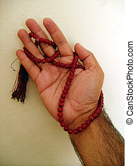 Praying Hand - A hand with rosary raised before god in...