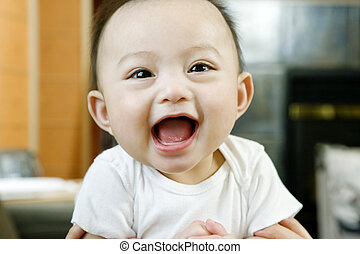 Baby Boy Laughing - Baby boy (6-9 months) held aloft,...