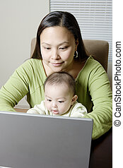 Mother And Baby On Laptop - Mother and baby son (6-9 months)...