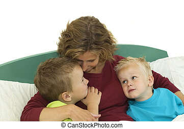 Happy Family - Mother and two sons lying happy in bed,...