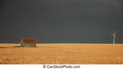 Kansas - A small old shack is seen across from a modern wind...