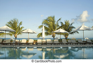 swimming pool at luxury resort with lounge chairs and...