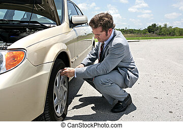 Flat Tire - Inconvenient - A businessman has a flat tire on...