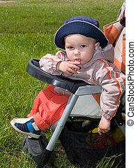 amused boy in stroller - amused boy sitting in stroller