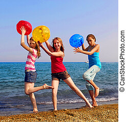 Girls on beach - Three girls with colorful beach balls...