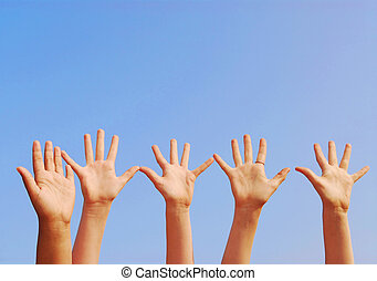 Hands - Raised hands on blue sky background with copy space
