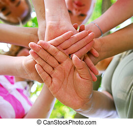 Hands of diverse group of teenagers joined in union