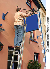 Hanging a New Sign - Middle aged man up a ladder hanging a...