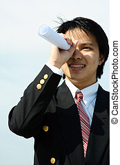 Business vision - A businessman looking through a rolled...