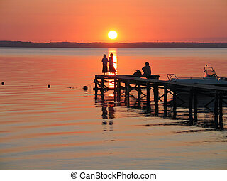 People on a dock in sunset in a camping site in Langeland...