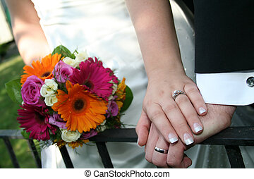 Wedding Hands 2 - A bride and Grooms hands with bouquet of...