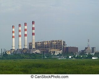 Gas driven power plant with four smoke stacks in a green...