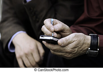 pda - two businessmen work on gadget (focus point on...