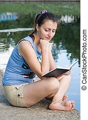 girl reads the book with river at background