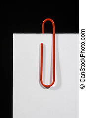 Paperclip - Red paper-clip on a white sheet, black...