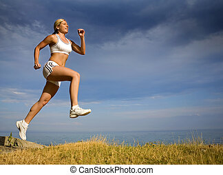 female runner - healthy athlete running on the beach in the...