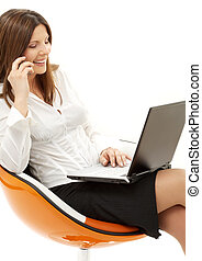 businesswoman with laptop and phone in orange chair over...