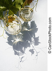 Wine and Vine - White wine with vine leaves and shadows on a...