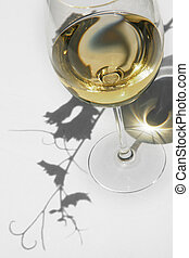 Wine and Vine - White wine with vine leaves shadows on a...