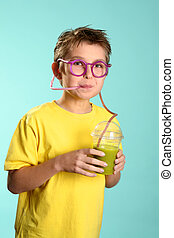 Making healthy foods fun - A boy sips a health juice...
