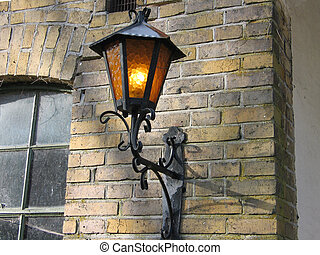 Old street lamp on bricks wall