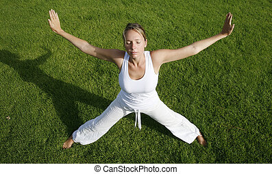 Outdoor Yoga - Woman in white in yoga position with green...