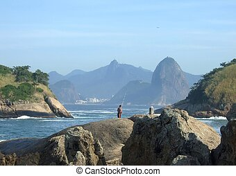 Fishing on the beach, with Christ Redeemer statue in...