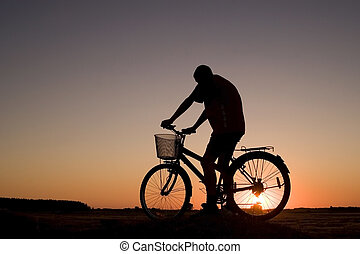 Biker silhouette - Man and bike silhouette in orange sunrise...