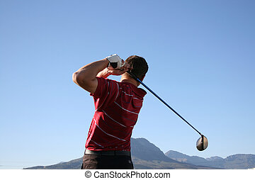 Driver Swing - Golfer shot with a driver against blue sky