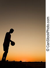 Football at sunset - sporman\\\'s siluetthe is playing...