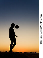 Football at sunset - spormans siluetthe is playing football...