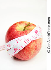 healthy living - Measurement tape wrapped around red apple -...