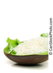 rice on a green leaf in a bowl of lumber