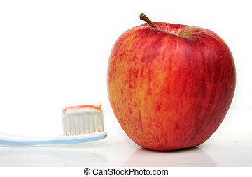 healthy teeth - a toothbrush with toothpaste and an apple in...