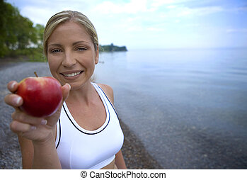 fresh apple and fitness - healthy athlete holding red apple...