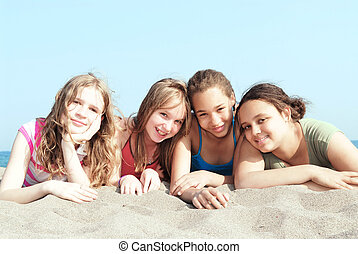Four girls on a beach - Portrait of four young girls on a...