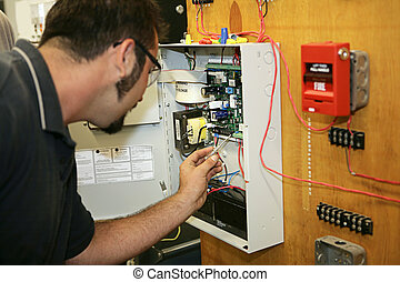 Working on Fire Alarm - A student electrician wiring a fire...