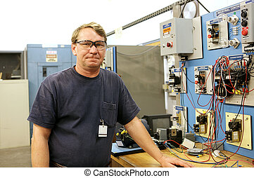Electrician at Motor Control Board - An electrician in a...