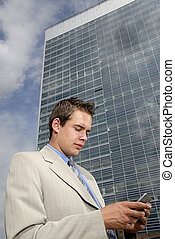 Young businessman with PDA in his hands in front of business...