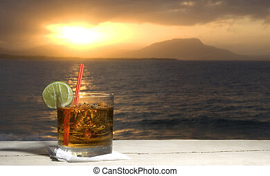 cocktail by the sea at sunset with island in distance