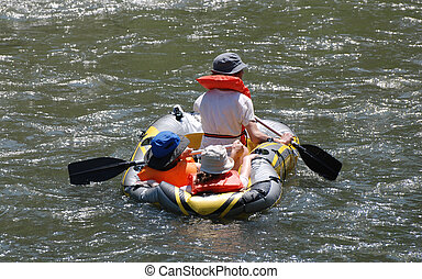 River Rafting - Three people floating down a river in an...