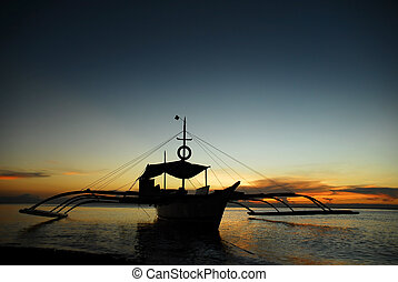 Boat in sunset - Asian fishermen\\\'s boat anchored on a...