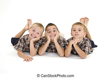 Brothers - Three Caucasian boys laying on a white background...