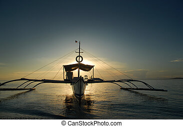 Boat in sunset - Asian fishermens boat anchored on a beach...