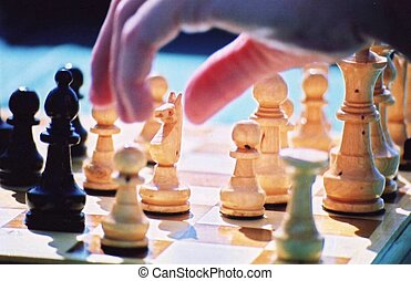 Game of Chess - Chess Pieces with a hand taking a turn