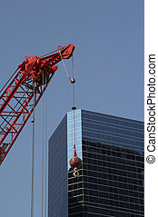 red construction crane before a modern office building