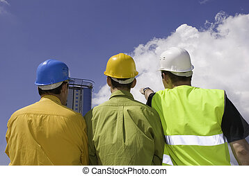 builders - three workers on sky background focus point on...